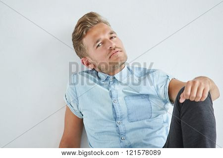 Brutal man in a shirt with short sleeves sitting in the chair his fists clenched slightly bent under