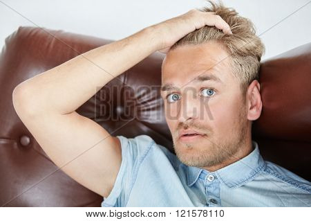 Brutal man in a shirt with short sleeves sitting in the brown chair holding hand behind the head clo