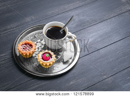Small cakes petit fours tartlets with jam and cream metal tray with white cup of coffee espresso on darck black wooden background empty clean place for your text