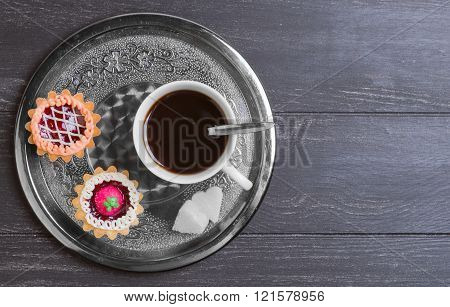 Small cakes petit fours tartlets with jam and cream metal tray with white cup of coffee espresso on darck black wooden background empty clean place for your text top view