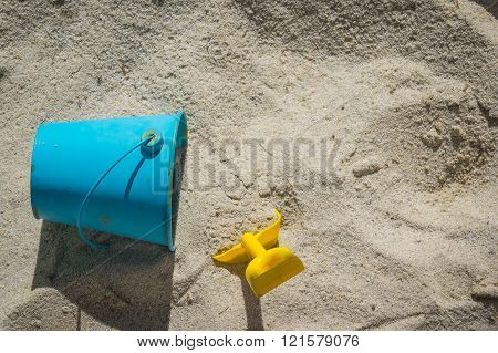 Childs blue pail and yellow shovel lying in the sand