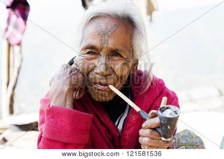 MINDAT, MYANMAR - DECEMBER 8, 2015: Photo of a Chin tribe tattooed faced woman (Muun tribe) smoking a pipe. Chin people, also known as the Kukis are a number of Tibeto-Burman tribal people.