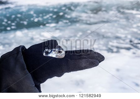 Piece of transparent beautiful ice lying on woman's hand at frozen lake Baikal