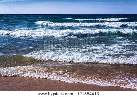 Blue Fresh Water Whitecap Waves Wash Ashore onto a Sandy Beach. Rhythm of Nature. Bright Clear Day. Seashore Background with Copy Space.