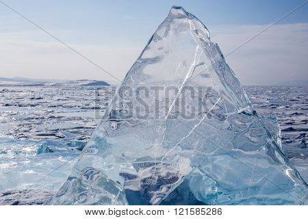 A transparent hummocks  on the surface of the blue frozen Lake Baikal. Horizon. Blue transparent ice