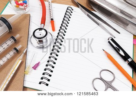 Red stethoscope, syringes, pen, and many colorful pills on blank notepad. Photo taken from above.