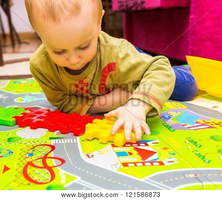 Boy Playing With Plastic Blocks In Home