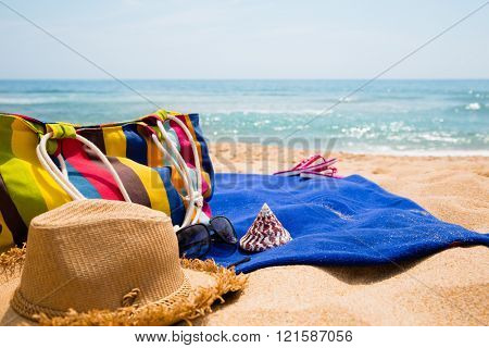 Women's beach items on the beach. Concept of summer vacations.