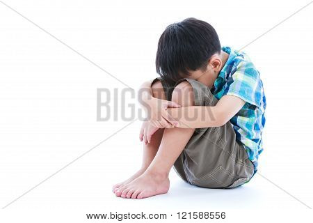 Little Sad Boy Barefeet Sitting On Floor. Isolated On White Background.
