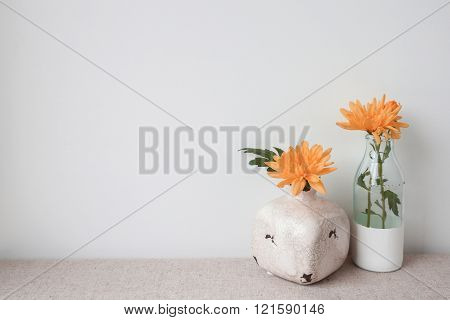 orange flowers in glass bottle and vase