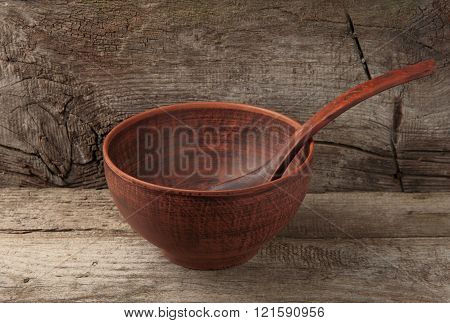 empty clay bowl with spoon on wooden background. Fasting. Lent.