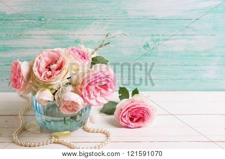 Pink Roses Flowers  In Blue Vase On White Painted Wooden Background Against Turquoise Wall.