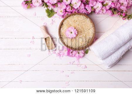Sea Salt In Bowl, Towels  And Pink Flowers On White  Wooden Background.