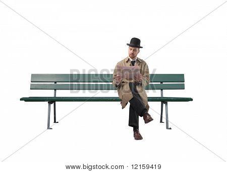 Gentleman reading a newspaper on a park bench
