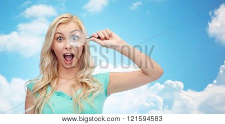 vision, exploration, investigation, education and people concept - happy smiling young woman or teenage girl looking through magnifying glass over blue sky and clouds background poster