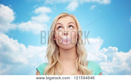 emotions, expressions and people concept - happy young woman or teenage girl chewing gum over blue sky and clouds background