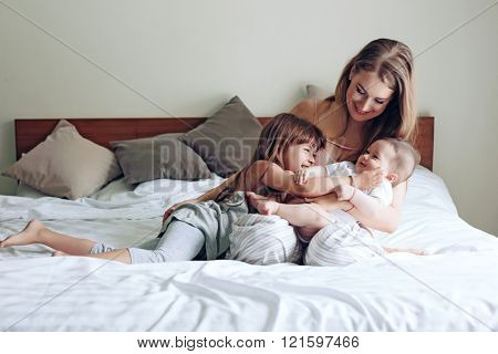 Young mom with her 5 years old daughter and 4 months old baby dressed in pajamas are relaxing and playing in the bed at the weekend together, lazy morning poster