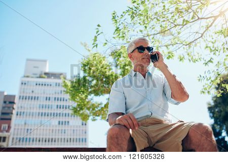 Mature Man Sitting Outdoors Talking On Cell Phone