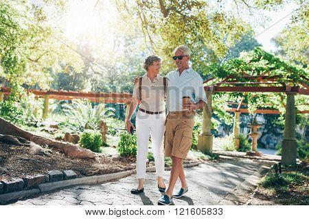 Happy Senior Couple Talking A Walk In Park