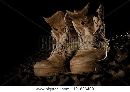 military boots on camouflage net and black backround
