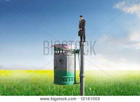 Businessman standing on a trash bin on a green meadow