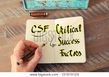 Retro effect and toned image of a woman hand writing a note with a fountain pen on a notebook. Business Acronym CSF as Critical Success Factors as business concept image poster