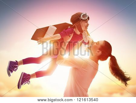 Mother and her child playing together. Little child girl plays astronaut. Child in an astronaut costume plays and dreams of becoming a spaceman. Happy loving family having fun. poster