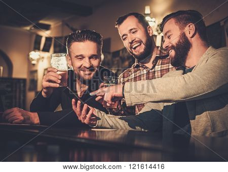 Cheerful old friends having fun with smartphone and drinking draft beer at bar counter in pub.