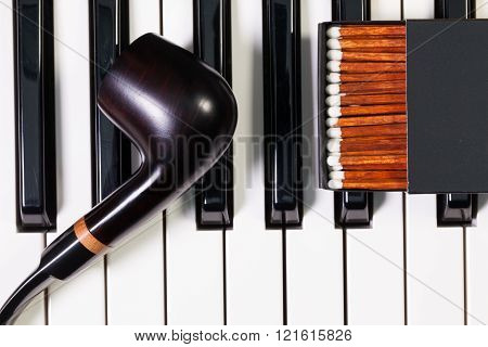 Detail of piano keyboard and luxury tobacco pipe