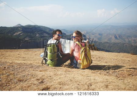 Couple of a cheerful man and woman travelers are sitting with map on a high mountain during their joint trip happy smiling male and female wanderers are enjoying their rest and amazing nature around