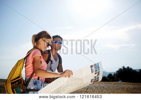 Beautiful couple of a wanderers are searching way on location map while standing on mountain hill in sunny day young female and male tourists are enjoying hike during joint summer adventure overseas
