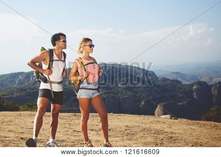 Young couple of a hikers are spending time together in the fresh air in beautiful sunny day during their recreation time man and woman wanderers are enjoying nature view while standing on a mountain