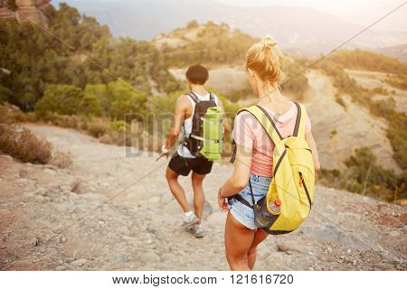 Young man and woman wanderers are walking in mountain during their summer vacation overseas two hikers with rucksacks on backs are exploring new places during their long awaiting amazing travel