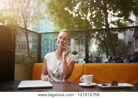 Young female with beautiful smile is talking on her mobile phone while she is relaxing in coffee shop in the fresh airbusiness woman is having pleasure cell telephone conversation during rest in cafe