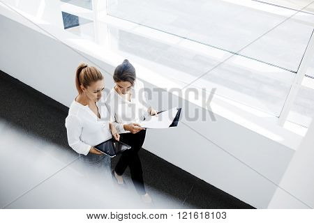 Young successful woman CEO is using portable digital tablet before meeting while her partner walking with paper documents in hand. Two female skilled managers searching on touch pad needed information