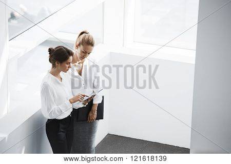 Two female entrepreneur is searching in internet via digital tablet needed information for meeting with foreign investors. Woman manager is holding touch pad while is standing with partner in office