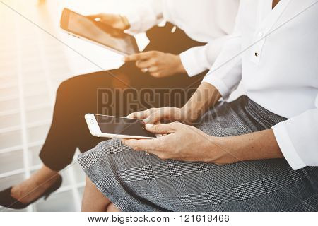 Two business people is chatting in web via mobile phonewhile her partner next to her is reading electronic book on touch pad.Two female are using cell telephone and digital tablet during break at job