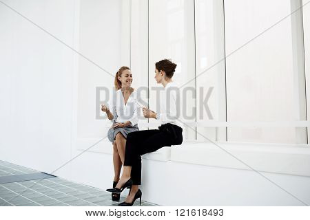 Young smiling female manager is listening story of her partner while they are sitting in modern office interior. Cheerful happy businesswoman is talking with secretary before conference with workers