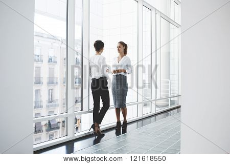 Two female proud leaders dressed in corporate clothes are discussing ideas before briefing with employees. Women entrepreneurs are talking about working moments while are standing near office window