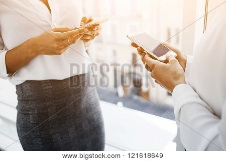 Two female are using their cellphones during work break
