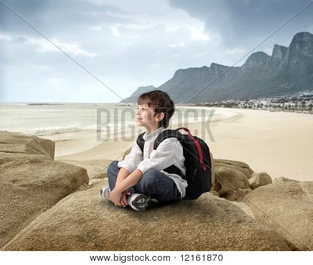 Smiling child sitting on a rock with seascape on the background