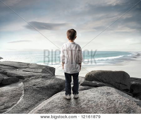 Child standing in front of a seascape