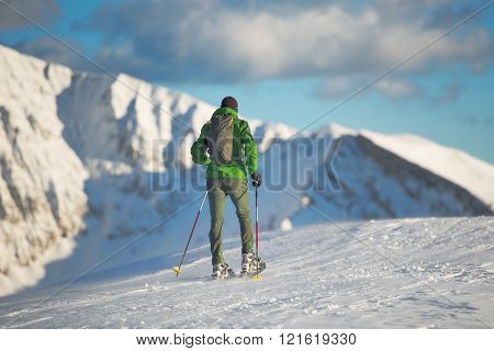 Mountaineer In Winter Landscape With Snowshoes.