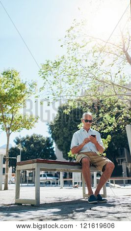 Mature Man Sitting Outdoor In City Using Mobile Phone