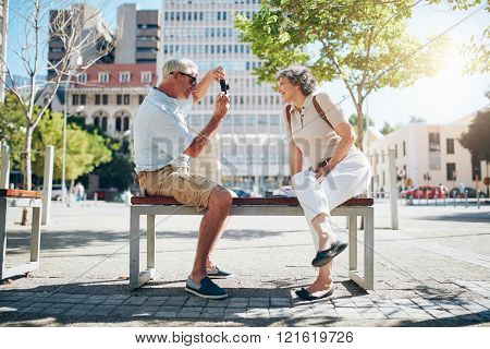 Senior Man Taking Pictures Of His Wife