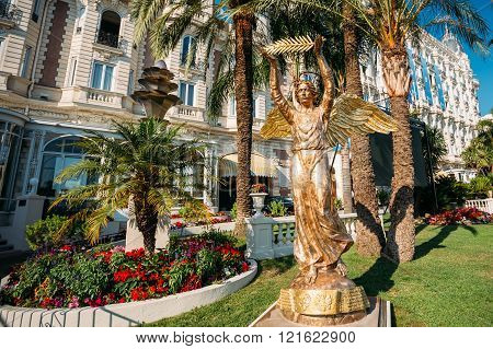 ronze statue of an angel with a palm branch in Cannes, France