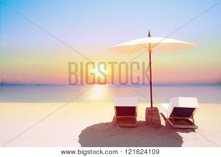 Tropical beach in sunset with beach chairs and umbrella