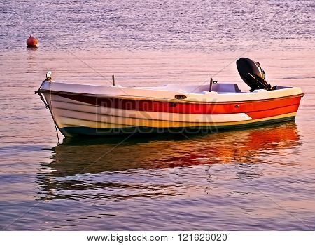 sunset reflection of a fishing boat on sea