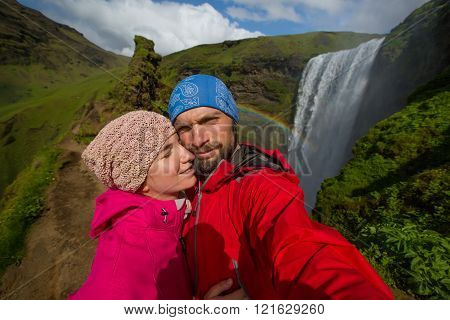 Skogafoss Waterfall during a sunny day, couple in love