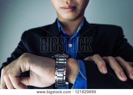 Close-up businessman looking at hand watch, selective focus